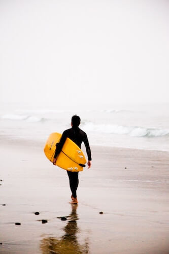 Man with surfboard in misty weather