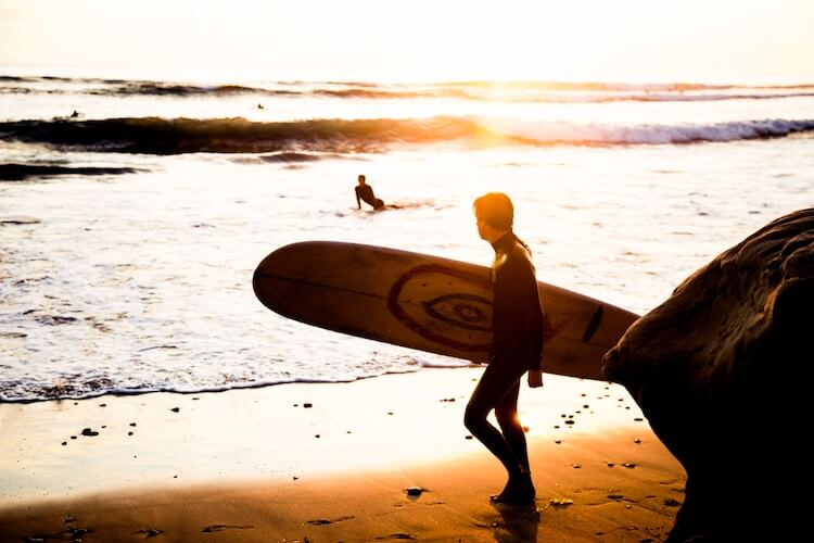 Man with surdboard at sunset